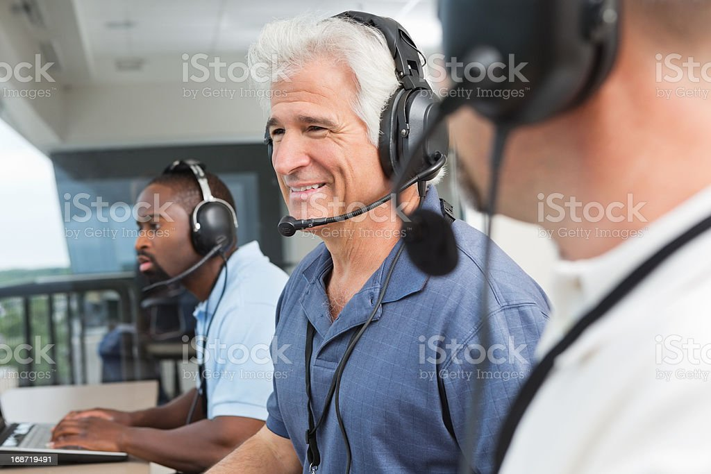 Happy sportscasters watching and calling sports game in press box stock photo