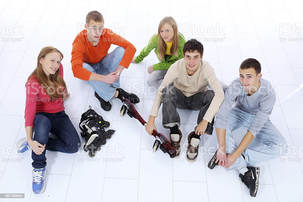 Happy sporty  teenagers sitting on the floor. royalty-free stock photo