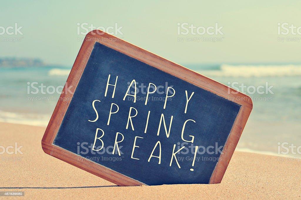 happy spring break in a blackboard on the beach stock photo