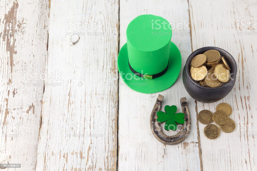 Happy St Patricks Day leprechaun hat with gold coins and lucky charms on vintage style white wood background. Top view stock photo