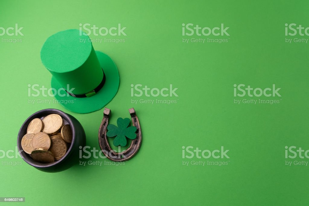 Happy St Patricks Day leprechaun hat with gold coins and lucky charms on green background. Top view stock photo