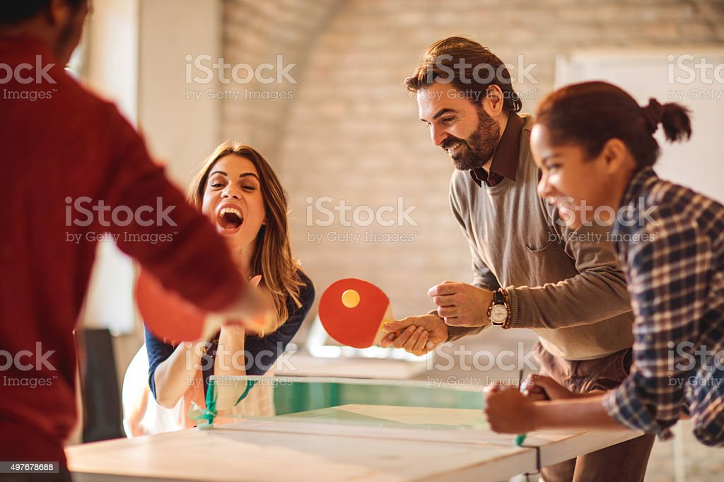 Group of happy business people playing table tennis at casual office....