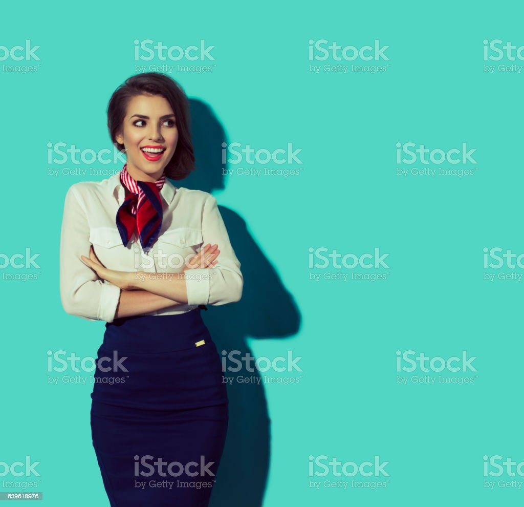 Happy stewardess looking right with crossed arms. Beautiful elegant hostess stock photo