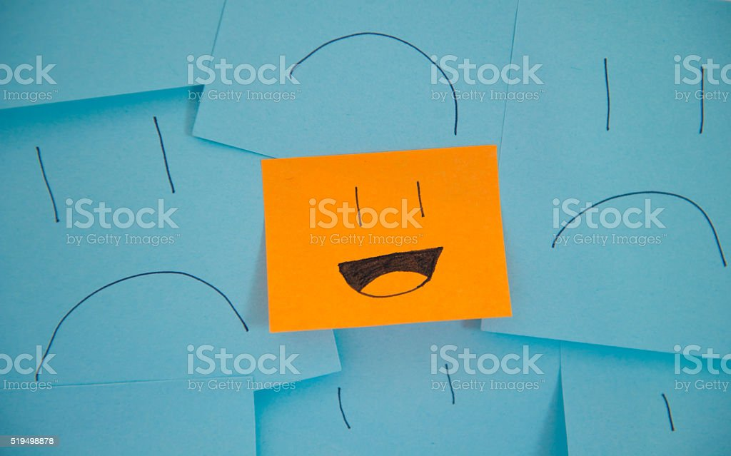 Happy Stick Note Amongst Sad Sticky Notes. stock photo