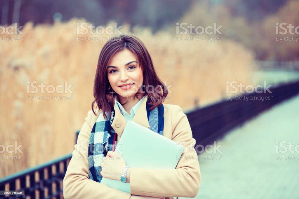 Happy student. Closeup portrait headshot professional beautiful confident young business woman holding computer isolated park cityscape outdoor background. Multicultural mixt race asian russian model stock photo