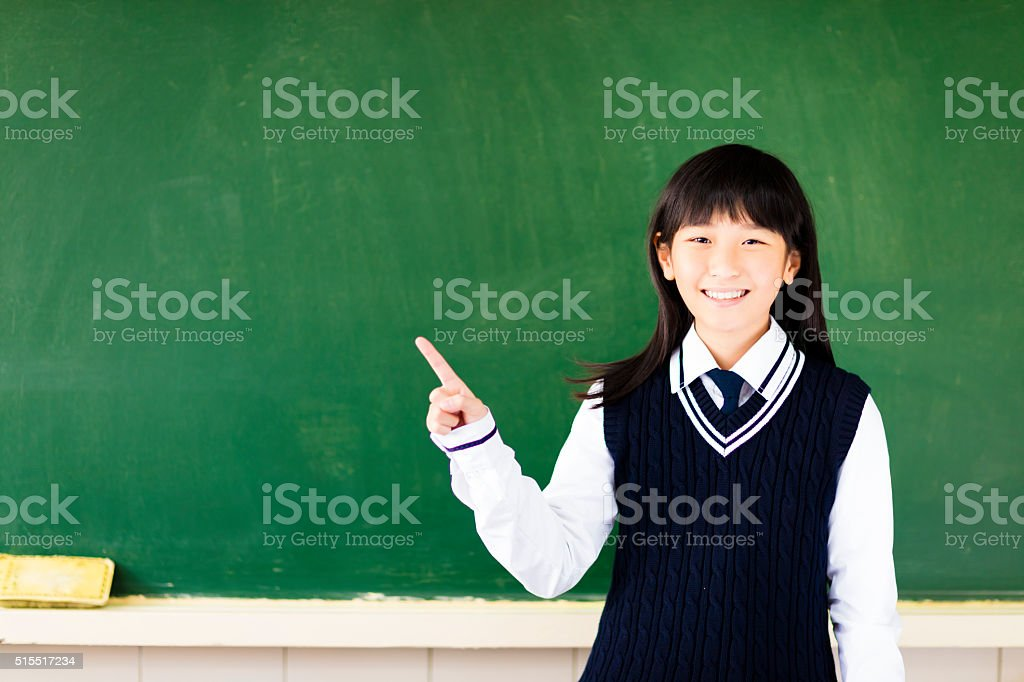 happy student girl with pointing gesture in classroom stock photo