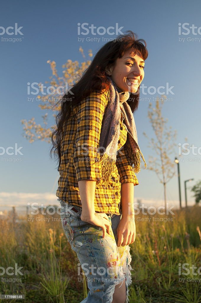 Happy student girl with yellow shirt jeans scarf in field royalty-free stock photo