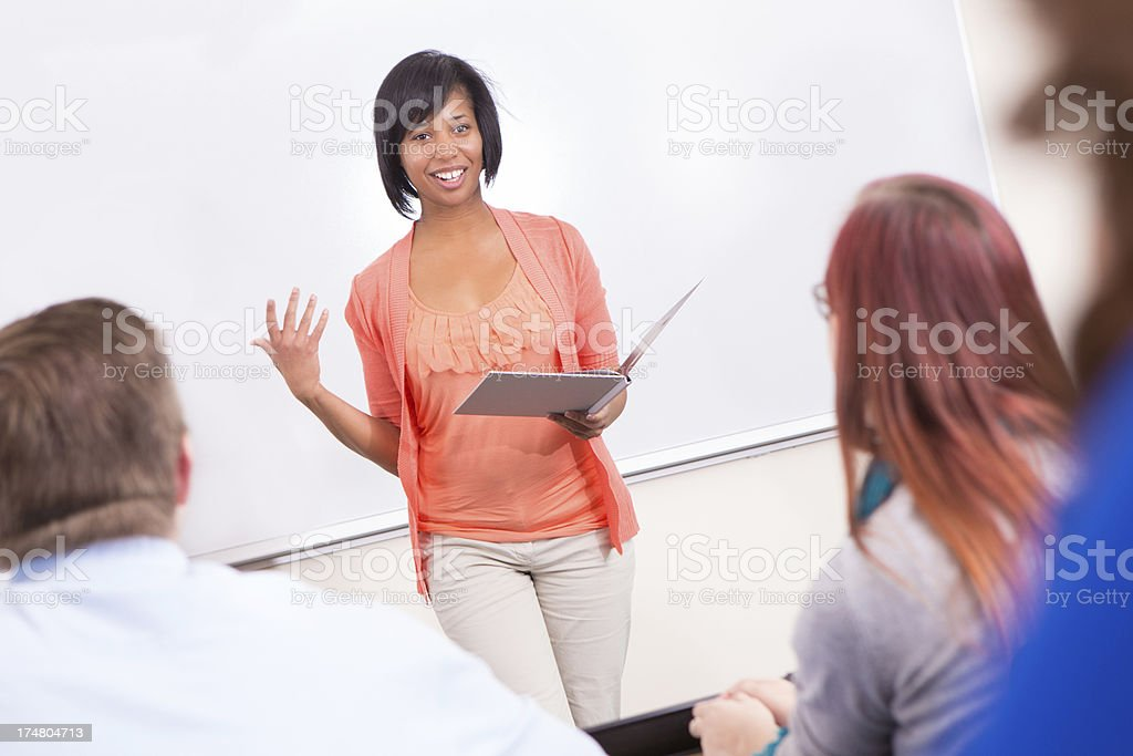 Happy student giving public speaking presentation speech in college classroom stock photo