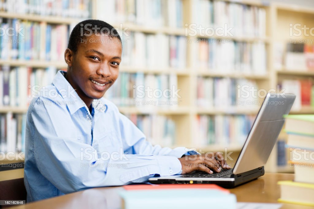 Happy student in library smiles up from his laptop royalty-free stock photo