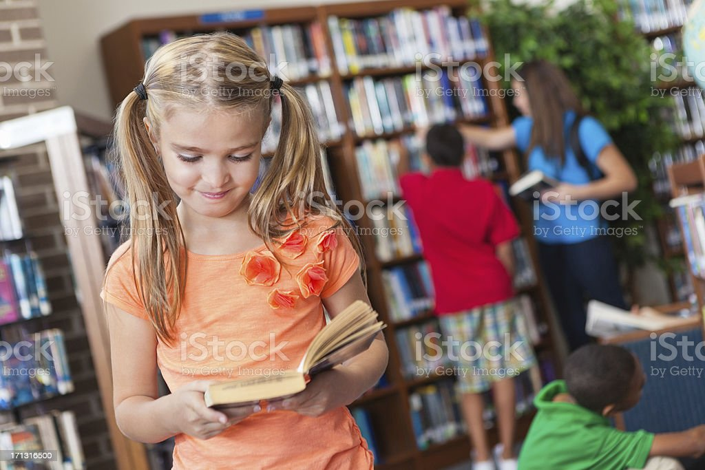 Happy student reading book in school library royalty-free stock photo