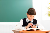 happy student reading smart phone in classroom