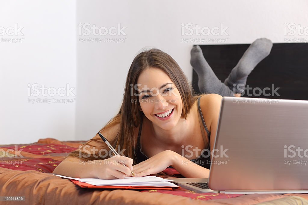 Happy student studying with a laptop in her bedroom stock photo