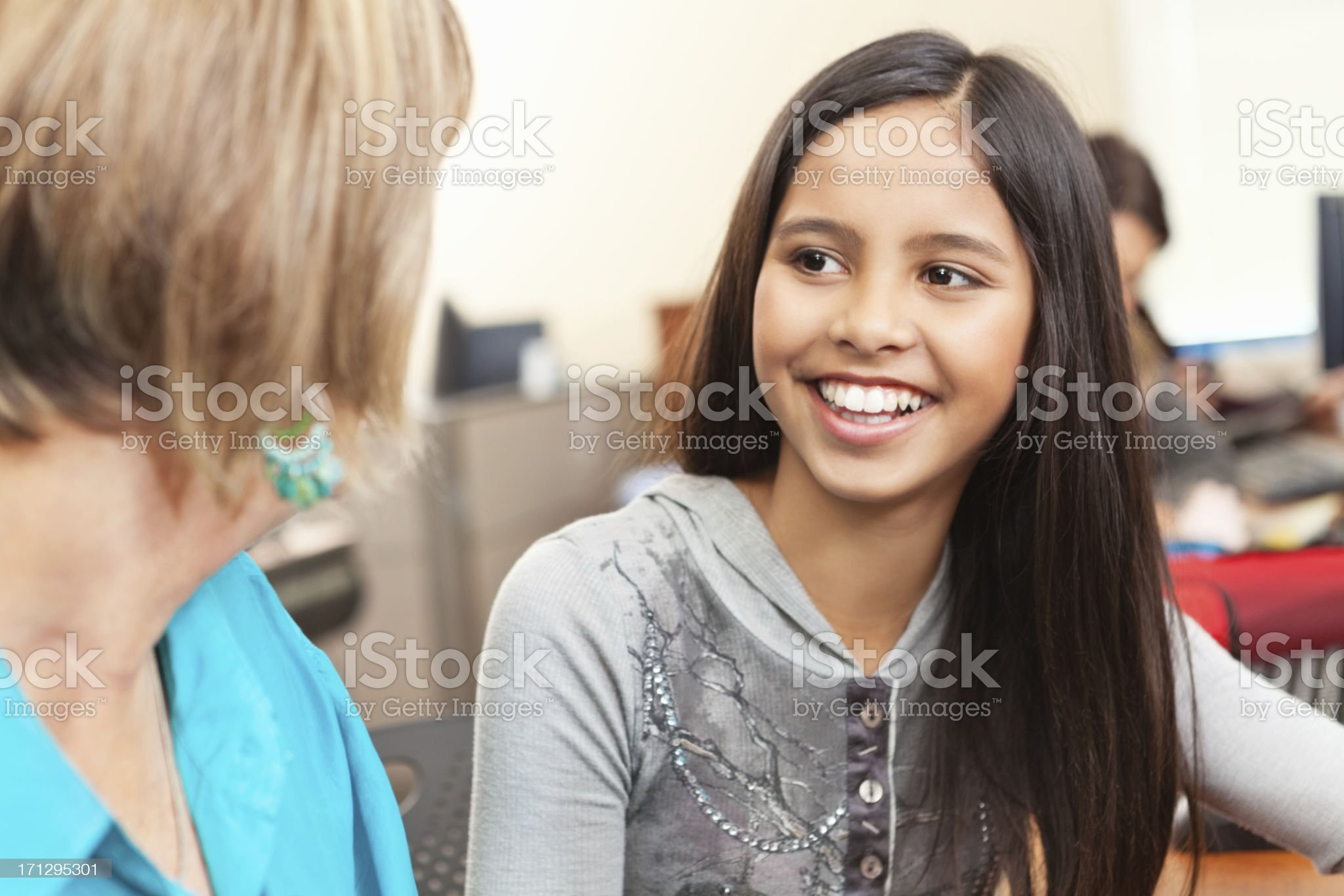 Happy student talking with teacher in computer lab classroom royalty-free stock photo