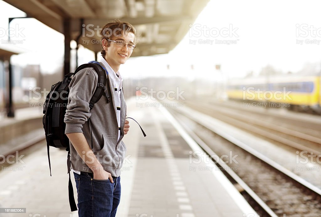 happy student waits for the train royalty-free stock photo