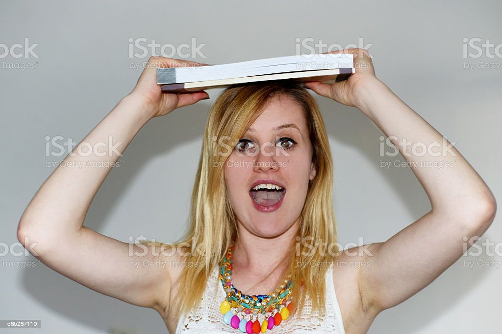 Happy student with books on her head stock photo