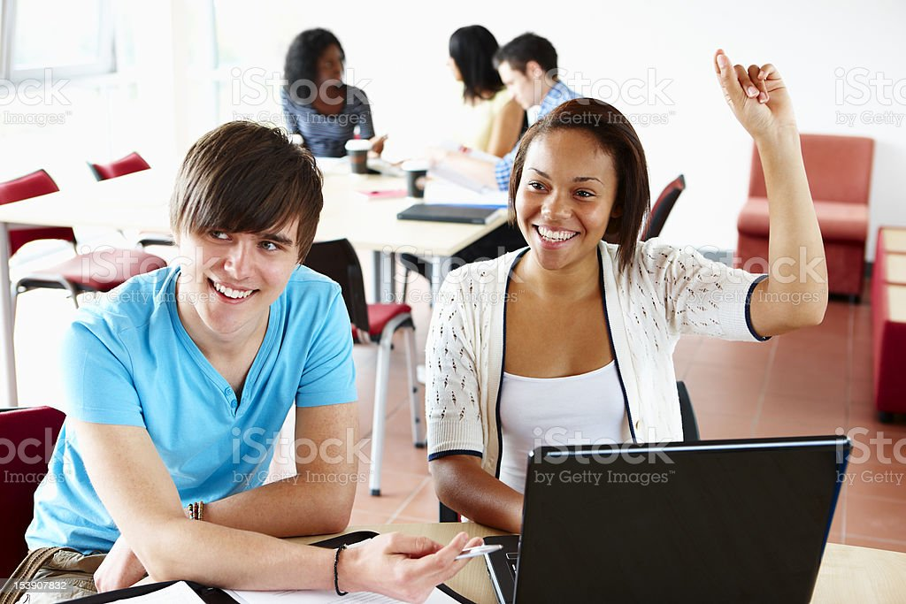 happy students in class studying on a laptop royalty-free stock photo