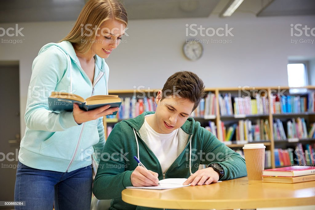 happy students preparing to exams in library stock photo