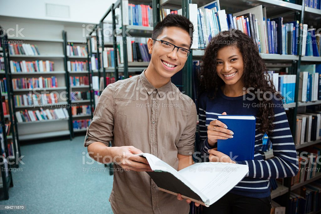 Happy students searching books in library stock photo