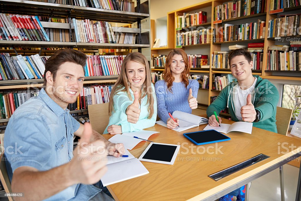 happy students showing thumbs up in school library stock photo