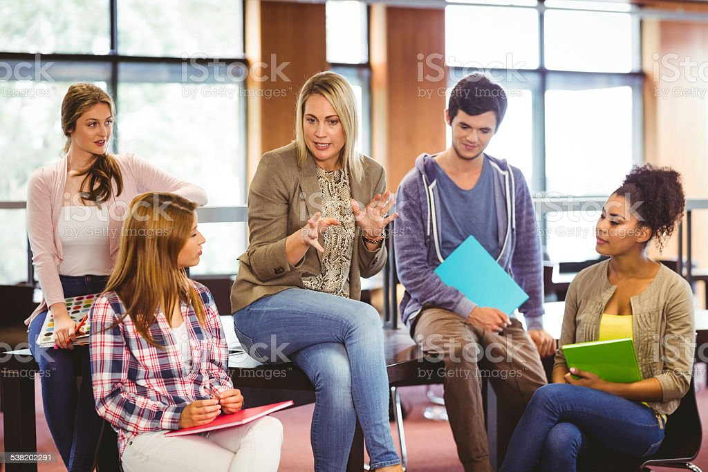 Happy students talking with their teacher stock photo