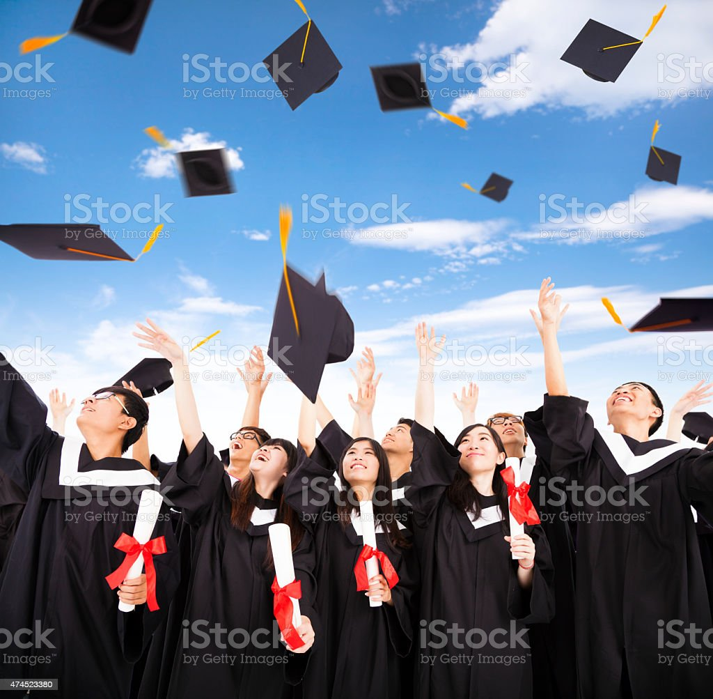 happy students throwing graduation caps into the Air stock photo
