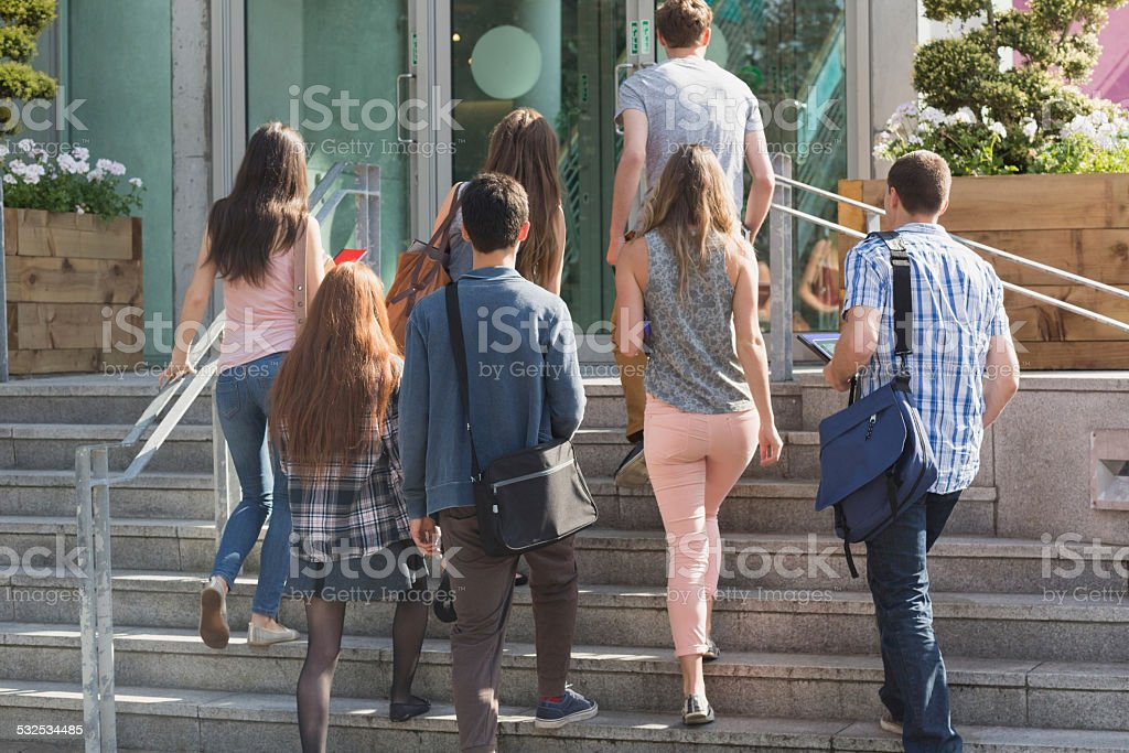 Happy students walking and chatting outside stock photo
