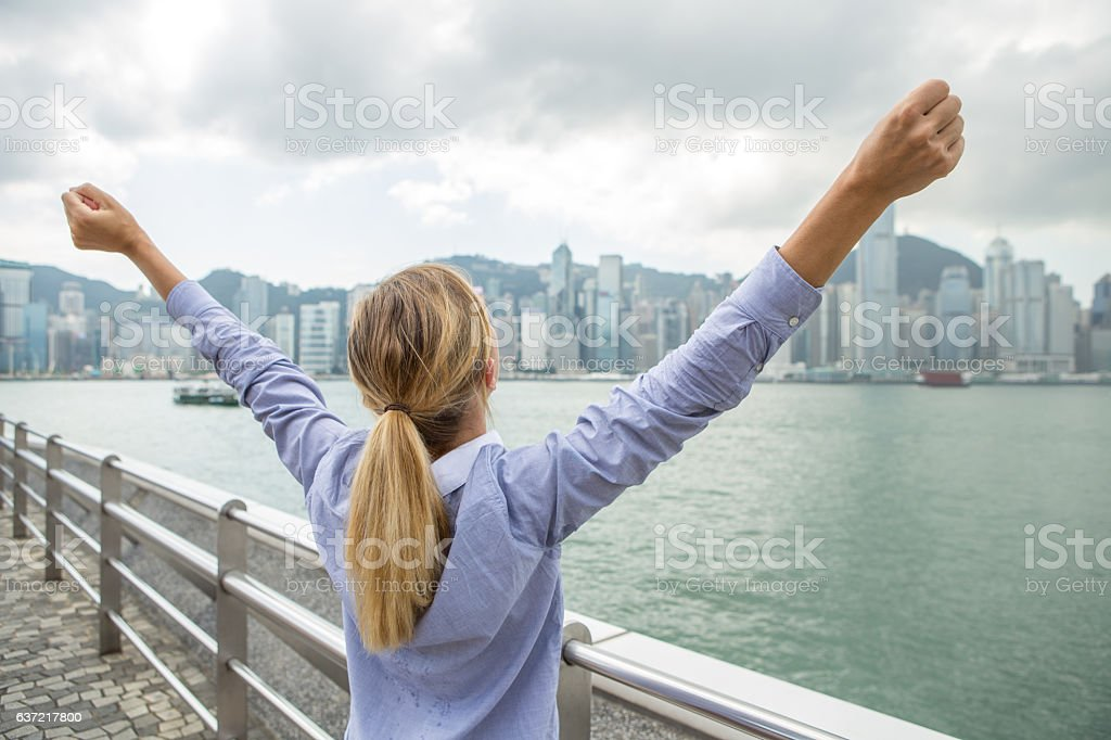 Happy successful business woman celebrating arms outstretched Hong Kong stock photo