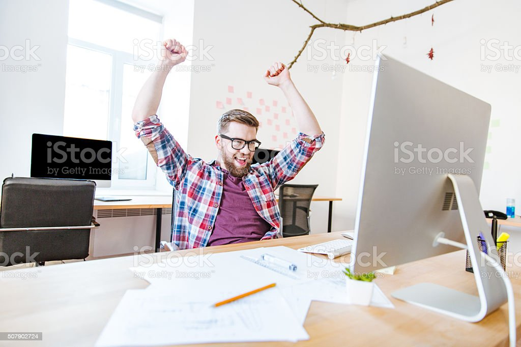 Happy successful man with raised hands sitting in office stock photo