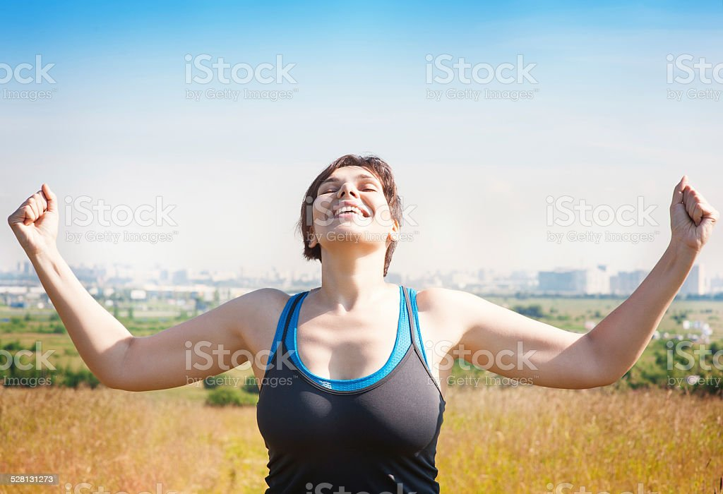 Happy successful plus size woman raising arms to the sky stock photo