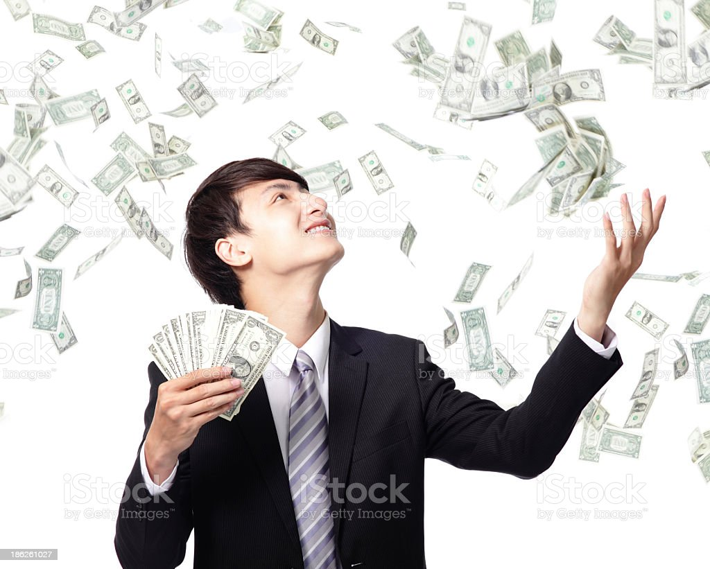 Happy suited man throwing money into the air stock photo