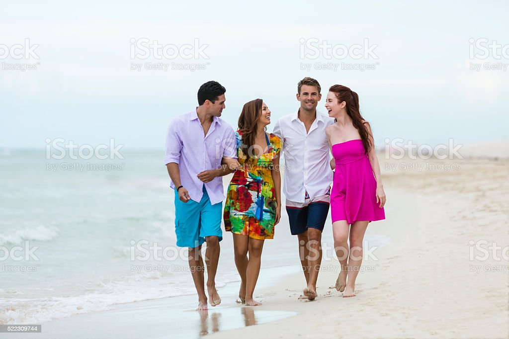 Happy summer couples walking on the beach stock photo