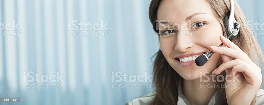 Happy support phone operator in headset at workplace stock photo