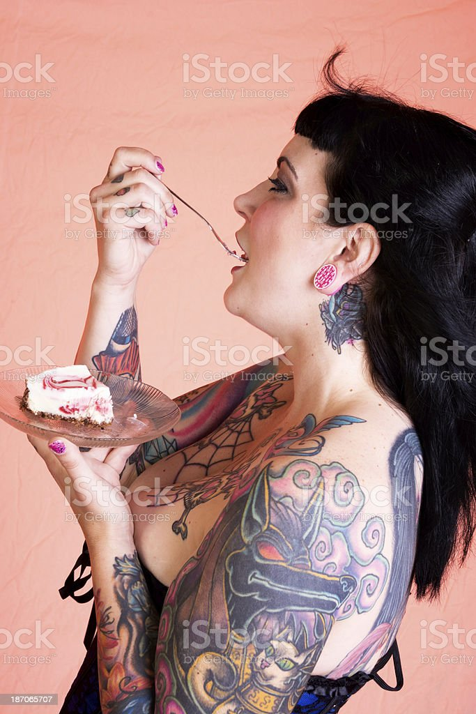 Happy tattooed woman with cheesecake on fork in mouth. royalty-free stock photo