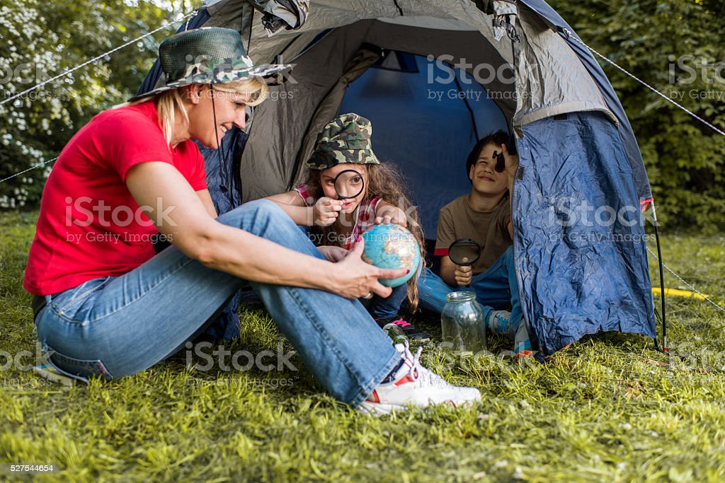 Happy teacher and two children on a camping in nature. stock photo