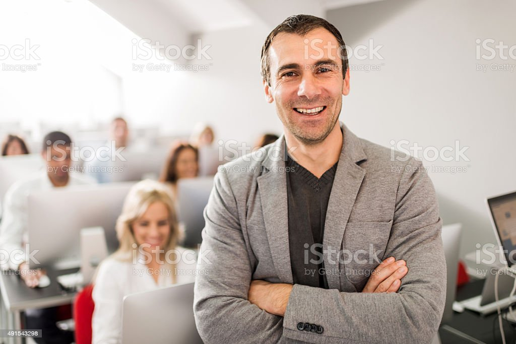Happy teacher at computer class looking at camera. stock photo