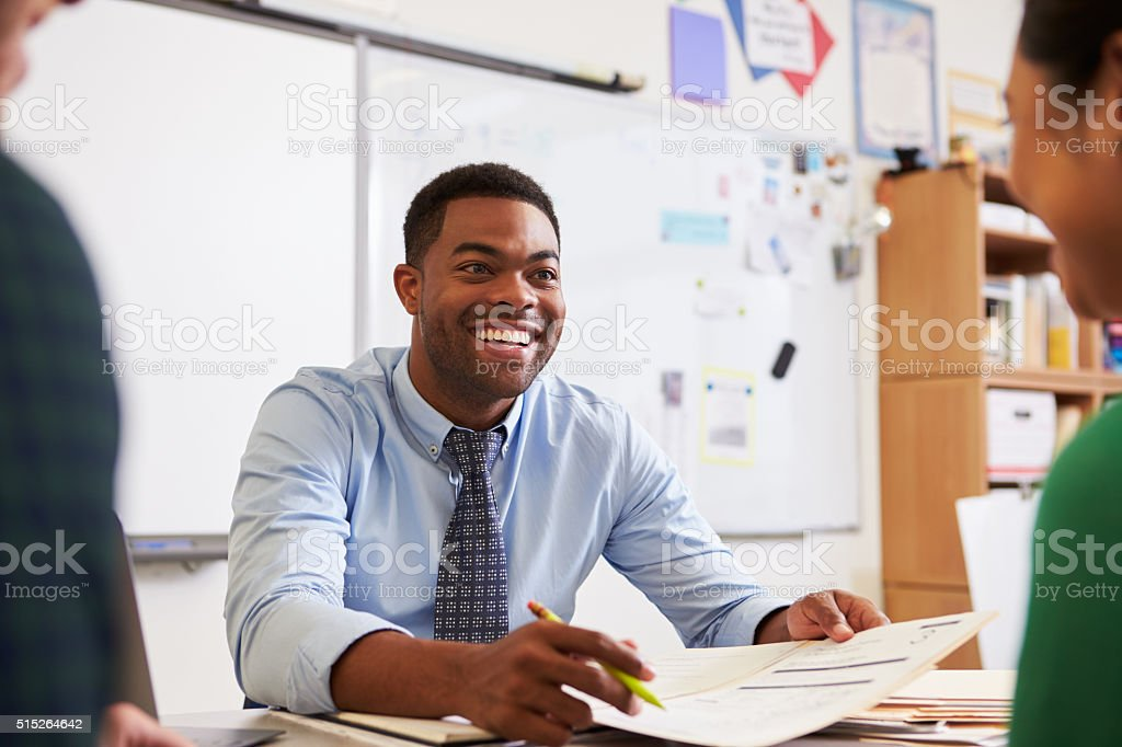 Happy teacher at desk talking to adult education students stock photo