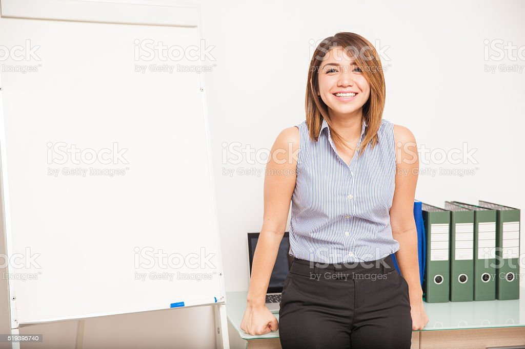 Happy teacher leaning on her desk stock photo