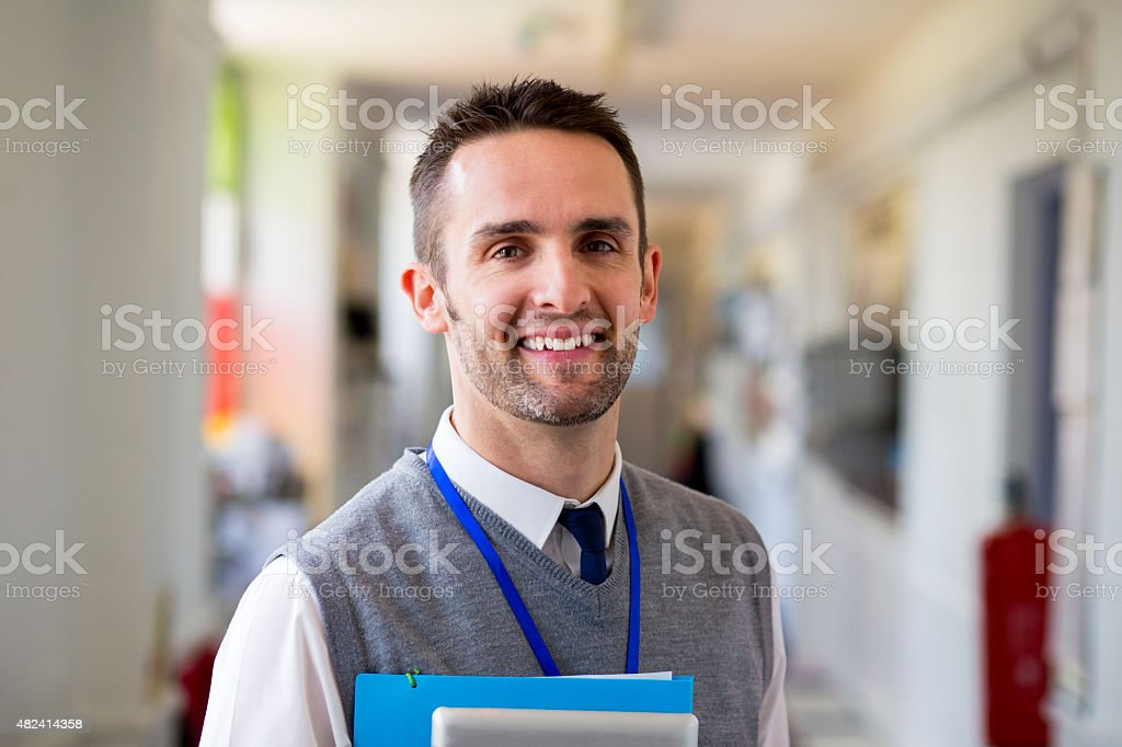Happy Teacher Standing in Corridor stock photo