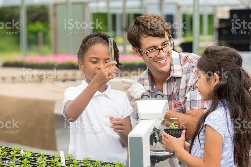 Happy teacher teaches students about botany stock photo