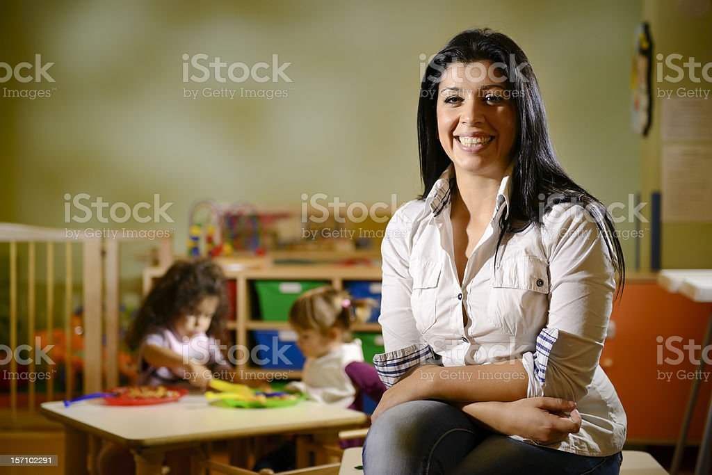 happy teacher with children eating in kindergarten stock photo