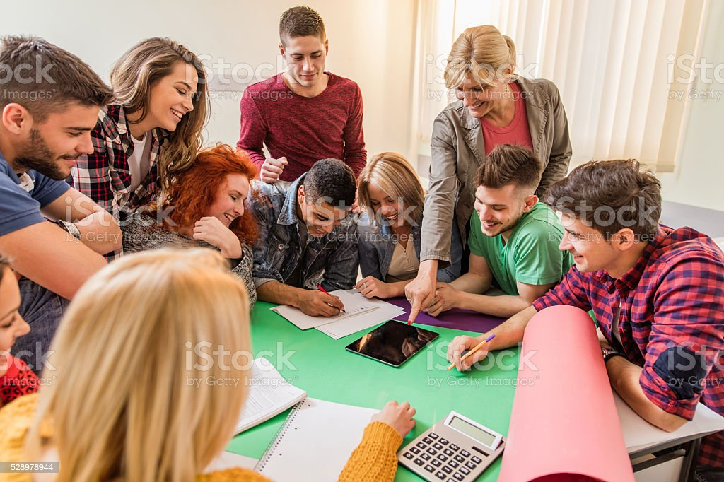 Happy teacher with group of students in the classroom. stock photo