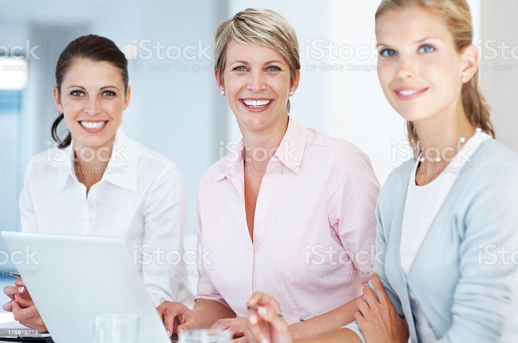 Happy team of businesswomen at office desk stock photo