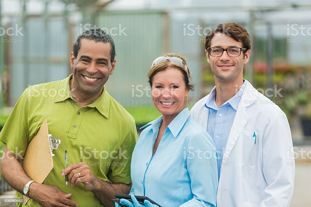 Happy team of scientists researching plants stock photo