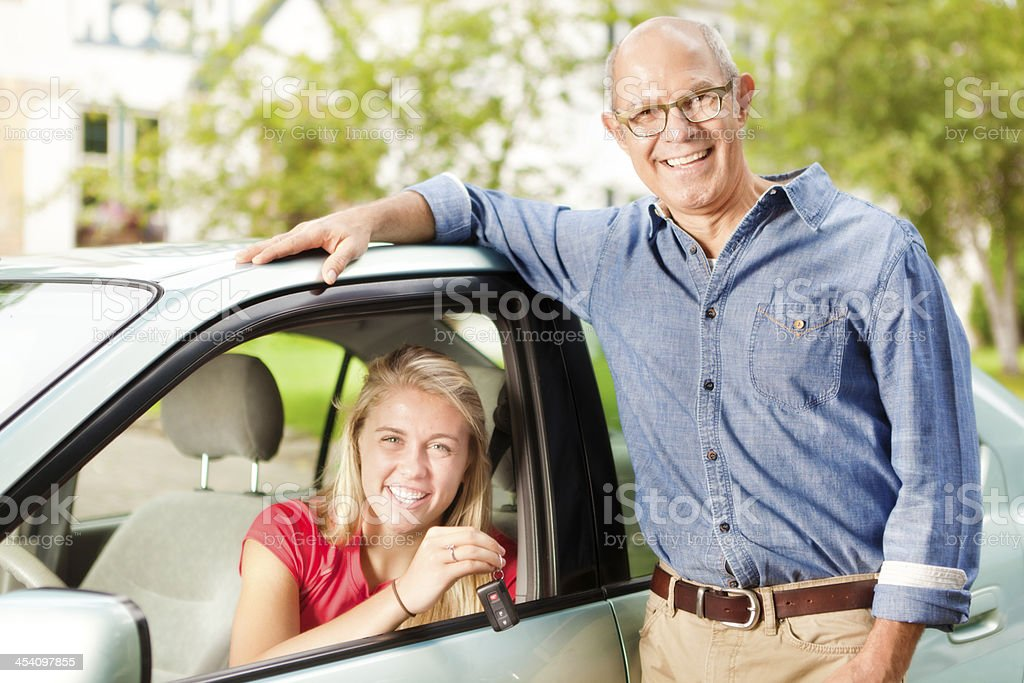 Happy Teen and Parent with Car Key to Vehicle stock photo