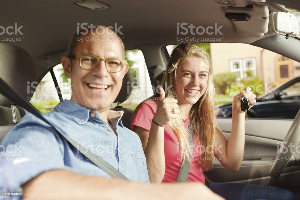 Happy Teen Driver with Her Parent and First Car stock photo