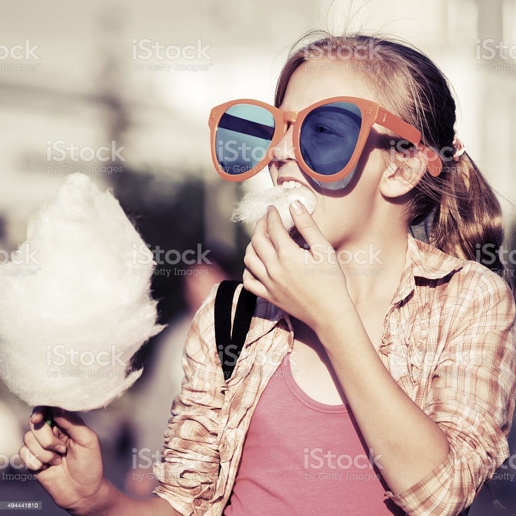 Happy teen girl eating cotton candy on a city street stock photo
