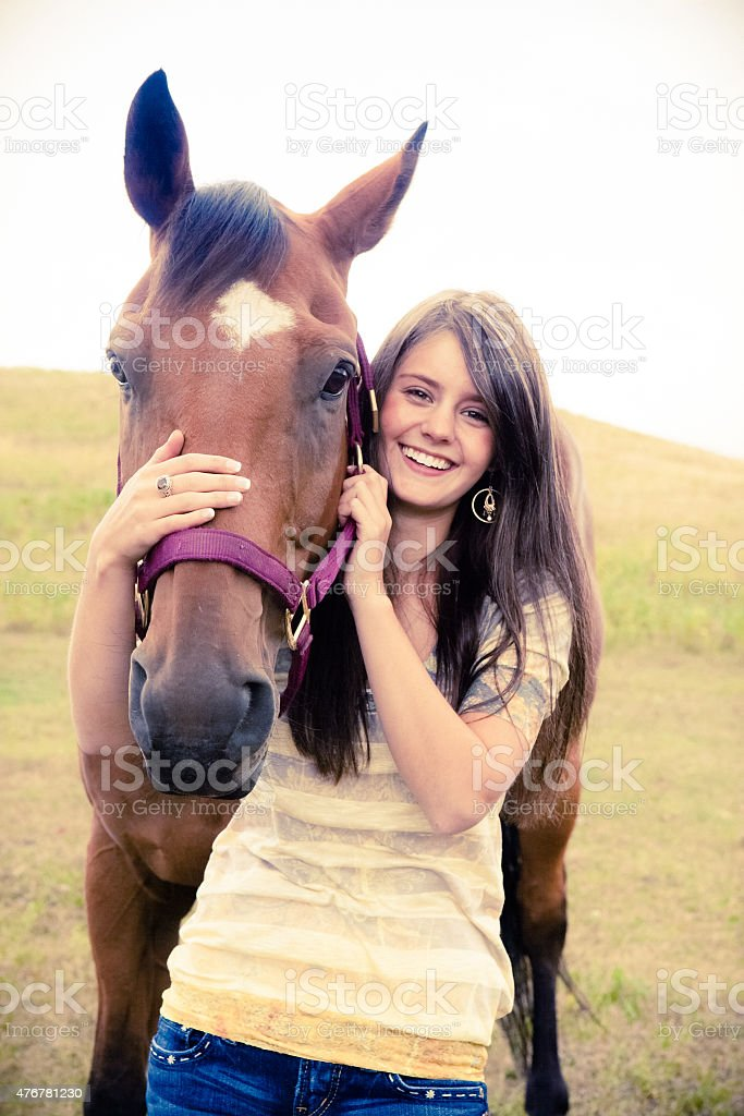 Happy teen girl smiling and by her horse stock photo