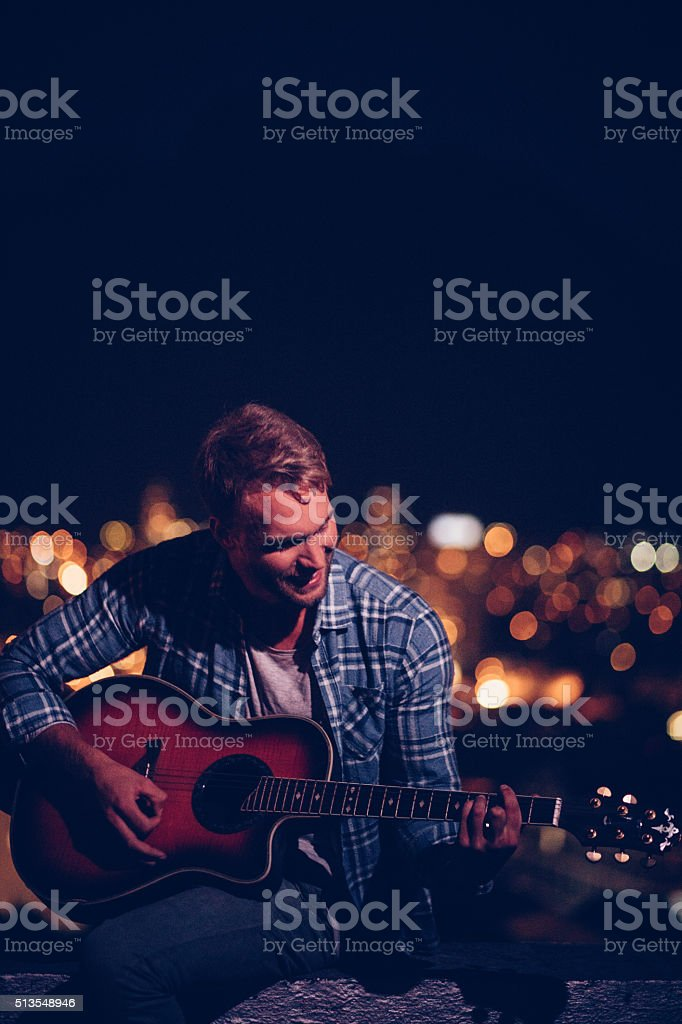 Happy teen guitarist playing outside on a rooftop stock photo