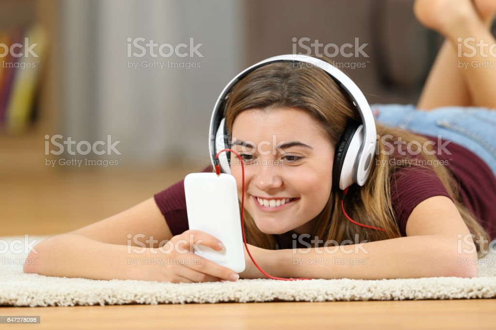 Happy teen watching media in a smartphone at home stock photo