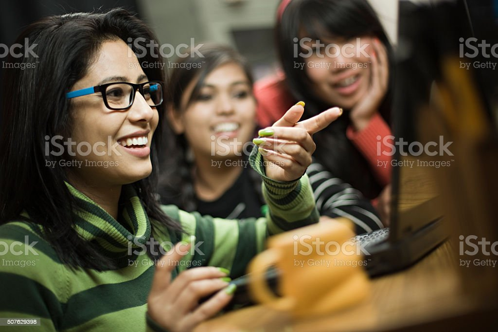 Happy teenage Asian girls of different ethnicity using laptop together. stock photo